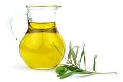 Olivenöl in der Glaskaraffe und im grünen Ölzweig lizenzfreie stockfotos