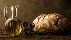 Olivenöl der Jungfrau im Weinleseölglas und im rustikalen Brot Stockfotos