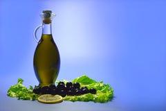 Olivenöl in einer transparenten Flasche, Oliven schwärzen mit einer Zitrone und Lizenzfreie Stockfotos