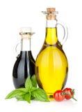 Olivenöl, Essigflaschen mit Basilikum und Tomaten Stockfotos
