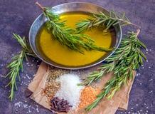 Olivenöl, frischer Rosmarin und Gewürze auf einem dunklen Hintergrund Stockbilder