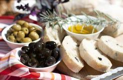 Olivenöl-, Grüne und Schwarzeoliven auf dem Tisch Stockfoto