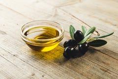 Olivenöl mit Blättern und Oliven Stockfoto