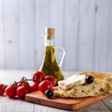 Olivenöl, Tomaten, Käse und Brot auf dem Tisch Lizenzfreie Stockfotografie