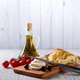 Olivenöl, Tomaten, Käse und Brot auf dem Tisch Lizenzfreie Stockbilder