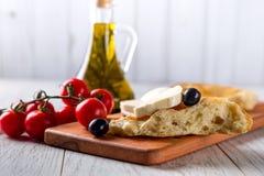 Olivenöl, Tomaten, Käse und Brot auf dem Tisch Lizenzfreie Stockfotos