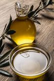 Olivenöl und Blätter auf einem Holztisch stockfotografie