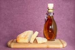 Olivenöl und geschnittenes Brot auf Schneidebrett Lizenzfreie Stockfotografie