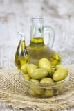 Olivenöl und grüne Oliven Stockbilder