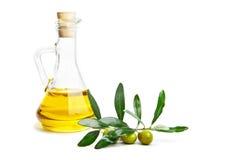 Olivenöl und Niederlassung mit Oliven auf Weiß Lizenzfreies Stockfoto
