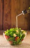 Olivenöl wird zum Salat gegossen lizenzfreies stockfoto