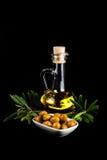 Olivenölflasche, grüne Oliven und Ölzweig Stockfotografie