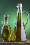 Olivenölflasche mit grünem Scheinwerferhintergrund Stockfotografie