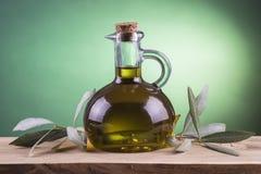 Olivenölflasche mit grünem Scheinwerferhintergrund Lizenzfreie Stockfotografie