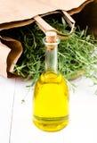 Olivenölflasche und -kräuter mit Papiertüte auf weißem hölzernem backg Lizenzfreies Stockbild