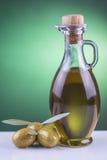 Olivenölflasche und -oliven auf grünem Hintergrund Lizenzfreie Stockfotos