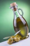 Olivenölflasche und -oliven auf grünem Hintergrund Lizenzfreies Stockbild