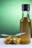 Olivenölflasche und -oliven auf grünem Hintergrund Stockbild