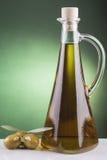 Olivenölflasche und -oliven auf grünem Hintergrund Lizenzfreies Stockfoto