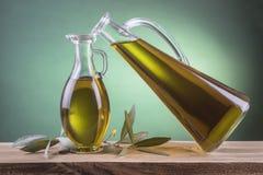 Olivenölflaschen auf einem grünen Scheinwerferhintergrund Stockfoto