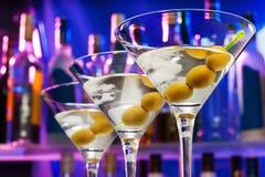 Oliven in den Cocktailgläsern und in den Barflaschen stockbild