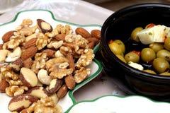 Oliven, Feta, Chips, Walnüsse, Mandeln, Acajounüsse, Paranüsse und Haselnüsse dienten mit einem Aperitif Stockbild