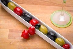Oliven im Teller mit einem Martini-Glas im Hintergrund Lizenzfreie Stockfotos