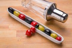 Oliven im Teller mit einem Martini-Schüttel-Apparat im Hintergrund lizenzfreies stockfoto