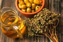 Oliven mit Paprika in einer keramischen Schüssel des Retrostils, im Zweig des getrockneten Basilikums und im Pitcher mit Olivenöl stockfotografie