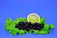 Oliven schwärzen mit einem Zitronen- und Blattsalat Lizenzfreies Stockbild