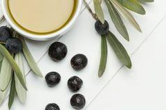 Oliven und eine Schüssel mit Olivenöl Stockfoto