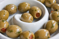 Olives. Stuffed green olives and a white swirl dish Royalty Free Stock Photos