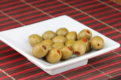 Olives. Green olives with red pepper on white plate Stock Photo