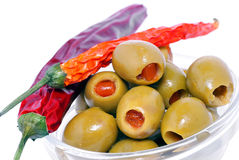 Olives. Green olives with red peppers in a glass bowl.Dried red pepper as garnish Stock Photo