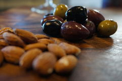 Olives and almonds. Food on wood board Stock Photo