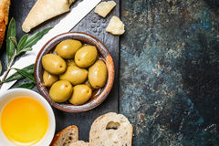 Olives appetizer with cheese, oil and ciabatta gut slices on dark rustic background, top view Stock Images