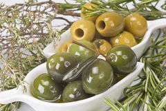 Olives and aromatic herbs. Two china spoons with green and pitted olives and some aromatic herbs Stock Images