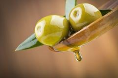 Olives avec de l'huile de baisse sur la cuillère en bois Image stock