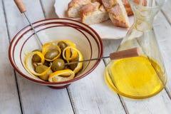 Olives avec le zeste de citron, l'ail et l'huile d'olive dans un plat d'argile photo stock