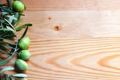Olives avec les feuilles vertes sur le fond en bois Image libre de droits