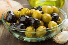 Olives, black and green in glass bowl Stock Photo