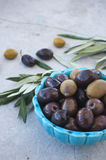 Olives in the blue ceramic bowl and green branch on a gray background Stock Photo