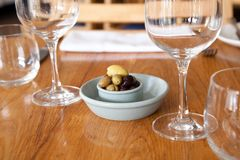 Olives in blue gray bowls on a wooden restaurant table. With views of wine glasses and table setting Stock Photo