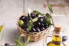 Olives and a bottle of olive oil on white  table. Olives and a bottle of olive oil on white  wooden table Stock Image