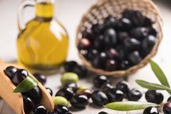 Olives and a bottle of olive oil on white  table. Olives and a bottle of olive oil on white  wooden table Royalty Free Stock Images