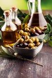 Olives. Bottle virgin olive oil and oil in a bowl with some oliv. Bottle virgin olive oil and oil in a bowl with some olives stock image