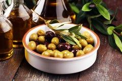 Olives. Bottle virgin olive oil and oil in a bowl with some oliv. Bottle virgin olive oil and oil in a bowl with some olives stock photography