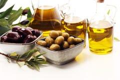 Olives. Bottle virgin olive oil and oil in a bowl with some oliv. Bottle virgin olive oil and oil in a bowl with some olives stock photos