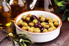 Olives. Bottle virgin olive oil and oil in a bowl with some oliv. Bottle virgin olive oil and oil in a bowl with some olives stock photo
