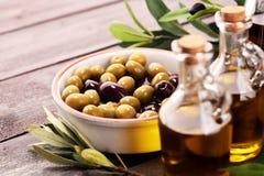 Olives. Bottle virgin olive oil and oil in a bowl with some oliv. Bottle virgin olive oil and oil in a bowl with some olives royalty free stock images